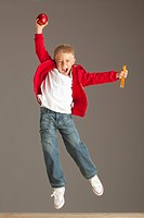 A Boy Leaping In The Air Holding A Snack In His Hands