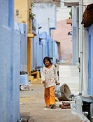 A Girl Walking Down A Street Between Rows Of Houses Holding A Plastic Bag, Sathyamangalam, Tamil Nadu, India