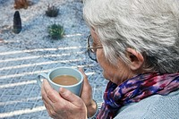 UK, Europe Senior woman holding a warm drink looking out of the window on a cold snowy day in winter