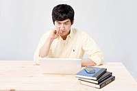Young man looking at laptop at table with iPhone and books