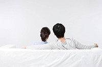 Back view of young couple sitting on sofa