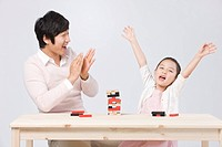 Father and daughter palying board game