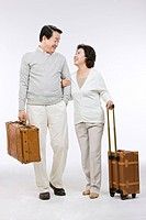 Senior couple holding suit cases