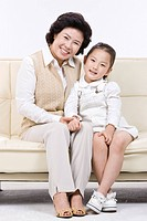 Grandmother and granddaughter sitting on sofa
