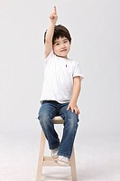 Boy sitting on stool pointing