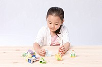 Girl playing with model houses at desk