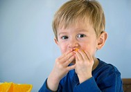 Adorable little boy eating orange