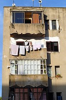 Woman hanging clothing from a balcony