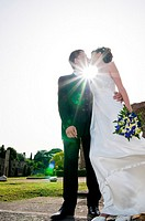 Wedding couple kissing against sunlight