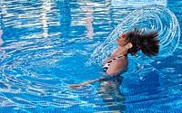 Women in the swimming pool, splashing around water with her hair