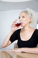Woman with gray hair drinking red wine