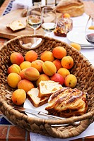 Apricot cake and fresh apricots in a basket plus white wine glasses