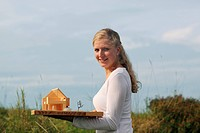 A woman outdoors holding an architect´s model of a house