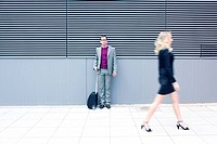 Young businessman looking at businesswoman walking by, blurred motion