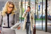 Businessman on cell phone walking near businesswoman, focus on background