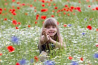 Little girl sitting in a wildflower meadow