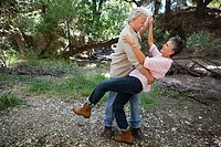 Mature couple dancing in forest