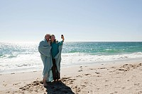 Couple at the beach in blanket, photographing themselves