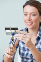 Young woman cutting credit card