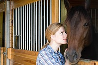 Mid adult woman with horse in stable