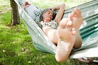 Mature woman sleeping barefoot in hammock (thumbnail)