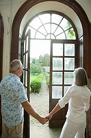 Mature couple holding hands by french doors