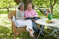 Mature couple outdoors looking at book