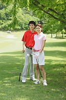 Man And Woman Looking At Camera On Golf Course