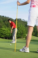 Couple Playing Golf On Golf Course