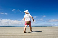 Little girl walking along a beach, Brittany, France, Europe