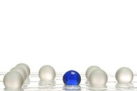 White balls and one blue ball on a game board, symbolic image for being different