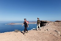 Hikers at Risco de Famara near Guinate, in front of La Graciosa Island, Lanzarote, Canary Islands, Spain, Europe