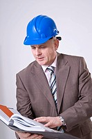 Man with hard hat looking into file