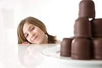 Girl sitting mischievously in front of a plate of chocolate marshmallows
