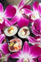 Pictured are 3 tuna and avocado sushi rolls on a silver platter with orchids around them