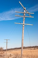 Slanted phone pole, broken wires, empty field and blue sky
