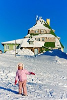 little girl in front of Masarykova Cottage, Orlicke Mountains in winter, Czech Republic