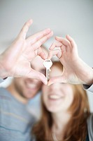 A happy couple holding a key