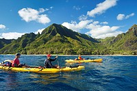 Hawaii, Kauai, Na Pali Coast, Group of kayakers paddling along coastline, Beautiful mountains in background. Editorial Use Only.