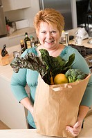 Woman with bag of vegetables in kitchen