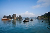 Floating Vietnamese fishing village with rocky coastline