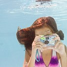 USA, New York, Girl 10_11 taking photo in swimming pool
