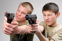 Two boys aiming with toy guns