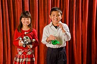 Asian boy and girl holding science experiments