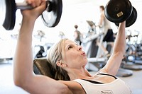 woman lifting free weights in fitness gym