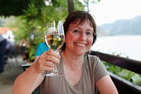 Woman with a glass of white wine at a beachside cafe on the Danube, Spitz, Wachau, Waldviertel, Lower Austria, Austria, Europe