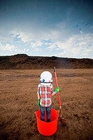 Boy wearing a space helmet and standing in a bucket at a landfill