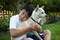 Mixed race boy hugging dog outdoors