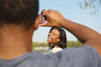 African American man taking photograph of wife outdoors