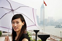 Chinese woman holding umbrella in the rain